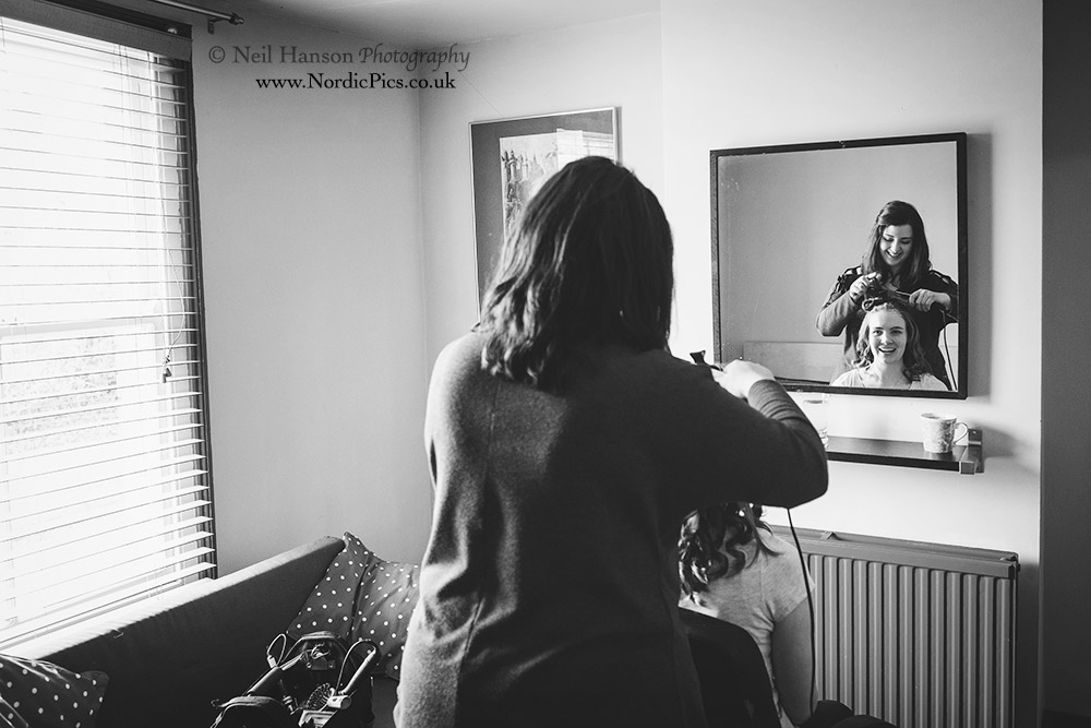 bride getting her hair done on the morning of her wedding